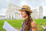 Happy female tourist in profile holding map, Piazza dei Miracoli