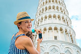 Smiling woman tourist taking photo of Leaning Tower of Pisa