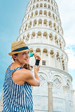 Happy female tourist taking photo of Leaning Tower of Pisa