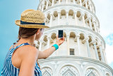 Woman seen from behind taking photo of Leaning Tower of Pisa