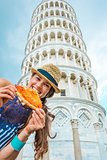 Woman biting slice of pizza by Leaning Tower of Pisa
