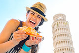 Laughing woman tourist holding slice of pizza in Pisa