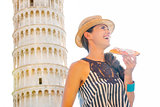 Smiling woman in profile with slice of pizza by Tower of Pisa