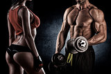 strong young couple working out with dumbbells. Shot in studio