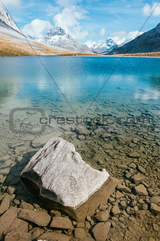 A transparent mountain lake with a stone
