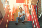 Stylish casual sexy man sitting on stairs.