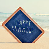 text happy summer in a chalkboard on the sand of a beach, with a