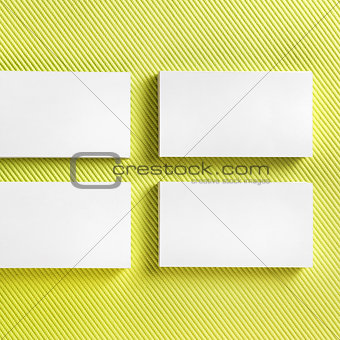 Blank business cards on green background.