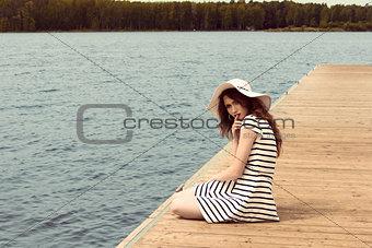 romantic girl on jetty near lake