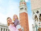 Happy mother and daughter on St. Mark's Square in Venice