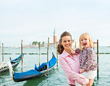 A happy mother holding her daughter in her arms in Venice