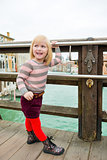 Happy blonde girl looking over shoulder on bridge in Venice