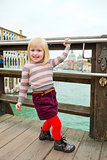 Happy, smiling blonde girl on bridge in Venice