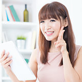 Asian girl using tablet showing peace hand sign