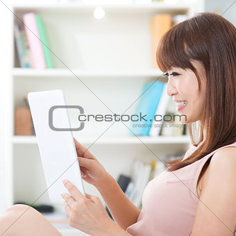 Asian female using touch screen tablet