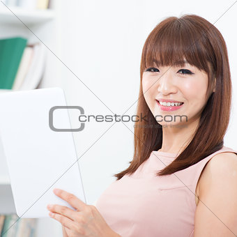 Asian woman using touch screen tablet