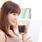 Asian girl drinking coffee while using tablet