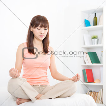 Asian girl meditating at home