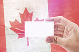 Man Holding Blank Business Card Against Canada National Flag