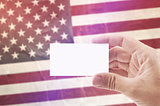 Man Holding Blank Business Card Against USA National Flag