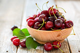 Wooden bowl with ripe cherries.