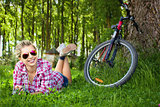 Young cyclist relaxation lying in the grass