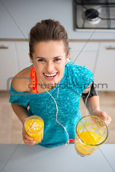 Athletic smiling woman holding freshly-made smoothie in kitchen
