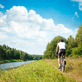 Cyclist Riding a Bike on River Bank