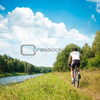 Cyclist Riding a Bike on River Bank