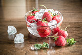 Fresh strawberries with ice cubes in the glass bowl