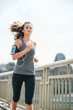 Long-haired woman jogging on bridge listening to music in summer