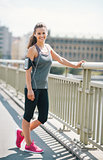 Smiling woman runner with pink shoes resting on bridge
