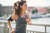 Jogging woman on bridge listening to music