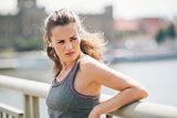 Woman jogger resting listening to music looking over shoulder