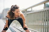 Woman jogger stretching on bridge while listening to music