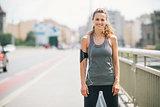 Smiling woman jogger standing still on bridge