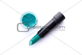 Top view of a lipstick and eye shadow in jar in bright teal gree