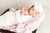 Newborn baby  with white headband laying in the basket