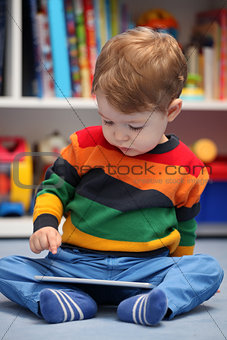 Happy 2 years old boy using a digital tablet computer