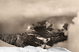 Sepia snowy mountains in clouds