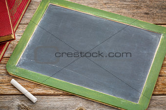 blank slate blackboard with chalk and books