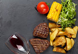 Beef steak with grilled potato, corn, salad and red wine