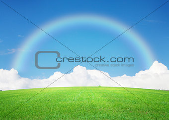 Green grass field, blue sky with clouds on horizon and rainbow