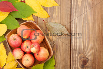 Apples in bowl and colorful autumn leaves on woden background