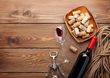 Red wine bottle, wine glass, bowl with corks and corkscrew