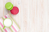 Colorful macarons and cup of milk