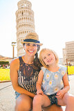 Happy mother kneeling with daughter sitting on her lap in Pisa