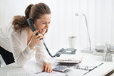 Happy businesswoman on telephone looking at document