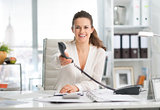 Smiling businesswoman at desk handing telephone over