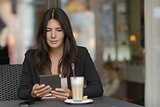 Woman relaxing in a coffee bar with her mobile